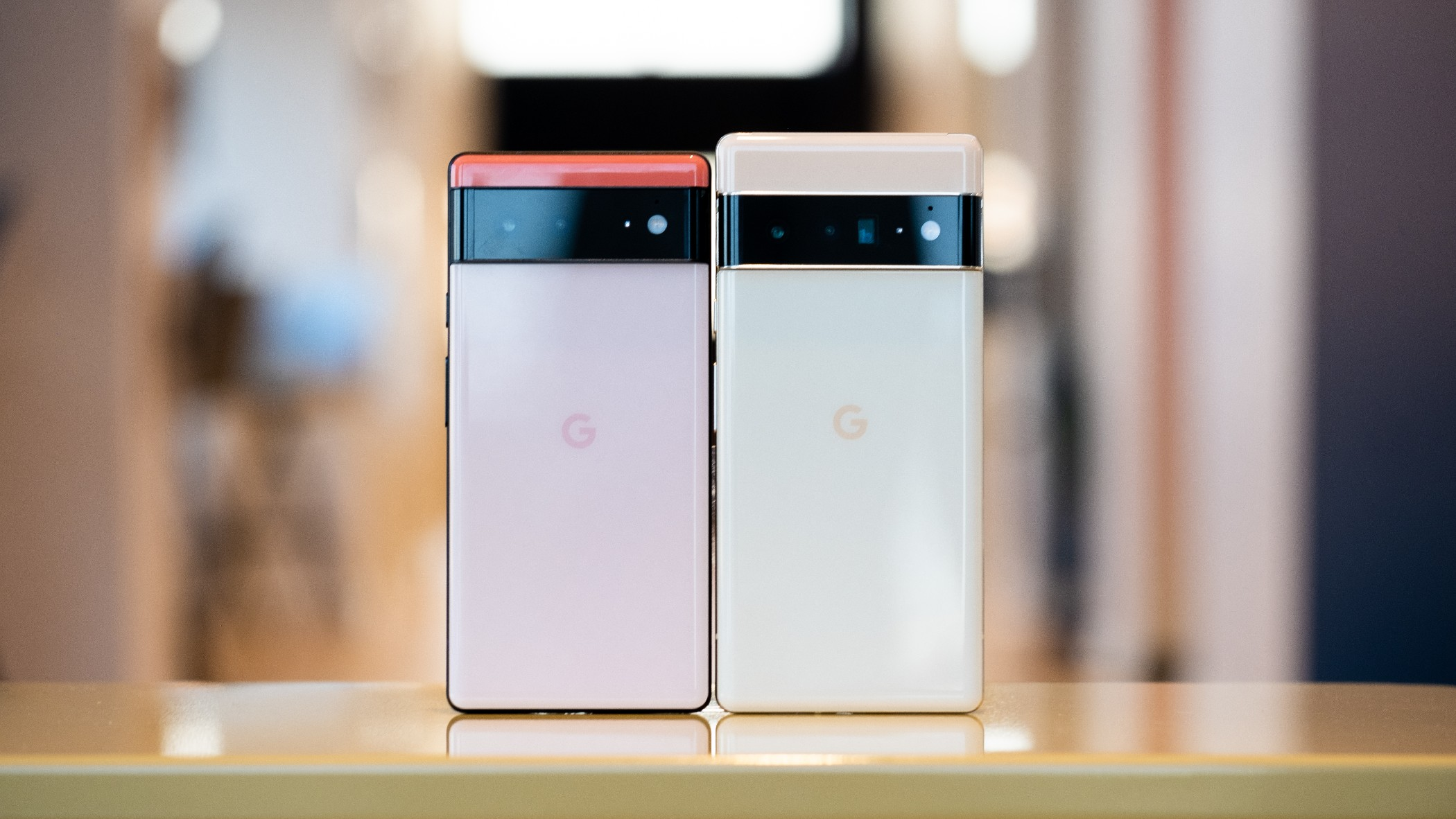 The Google Pixel 6 and 6 Pro on a table with their rear cameras facing out.